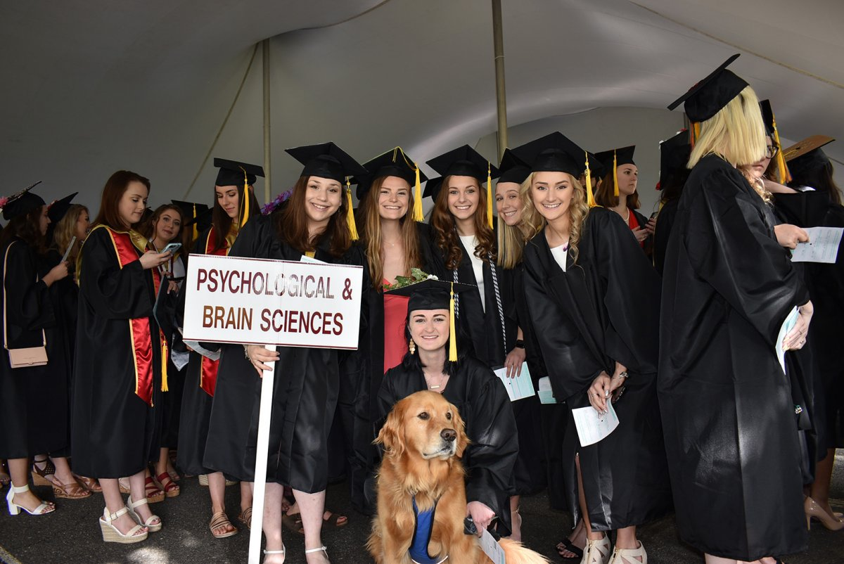 female graduates in gowns pose with golden retriever