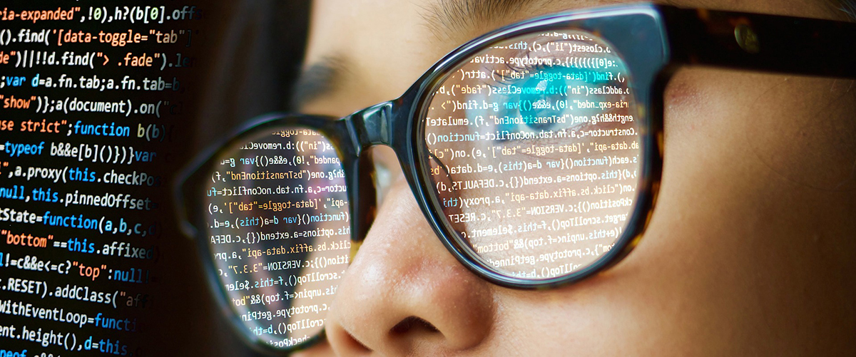 code on computer screen reflects onto persons glasses