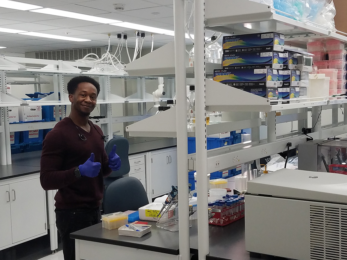 student gives thumbs up, working in lab for first time