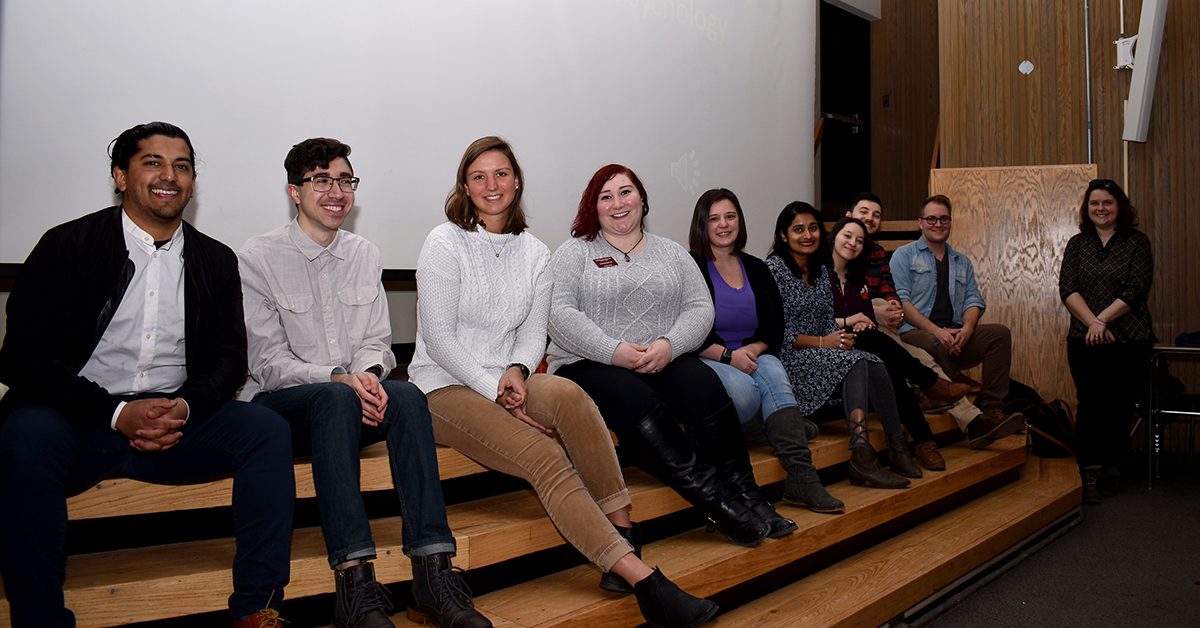 a group of recent alumni gather onstage to attend a psychology class