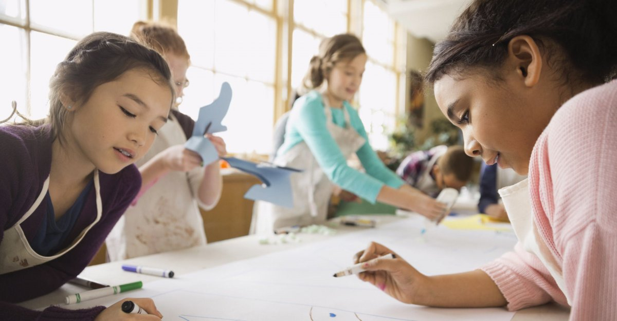 children drawing and cutting paper in classroom