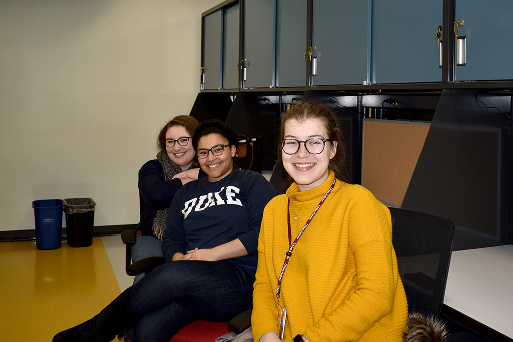 students smile in their new work cubicles