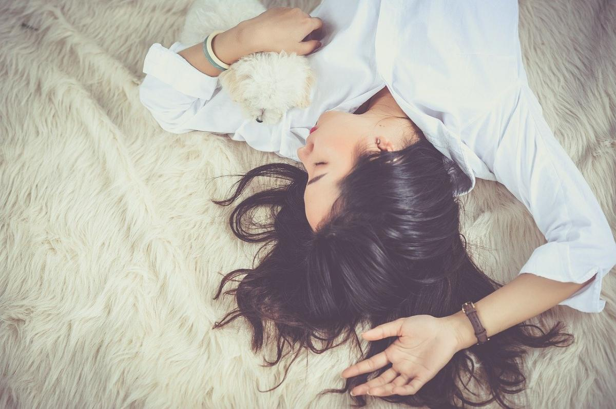 woman sleeping with small dog