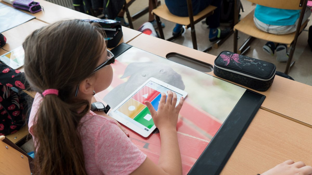 young girl uses ipad in classroom
