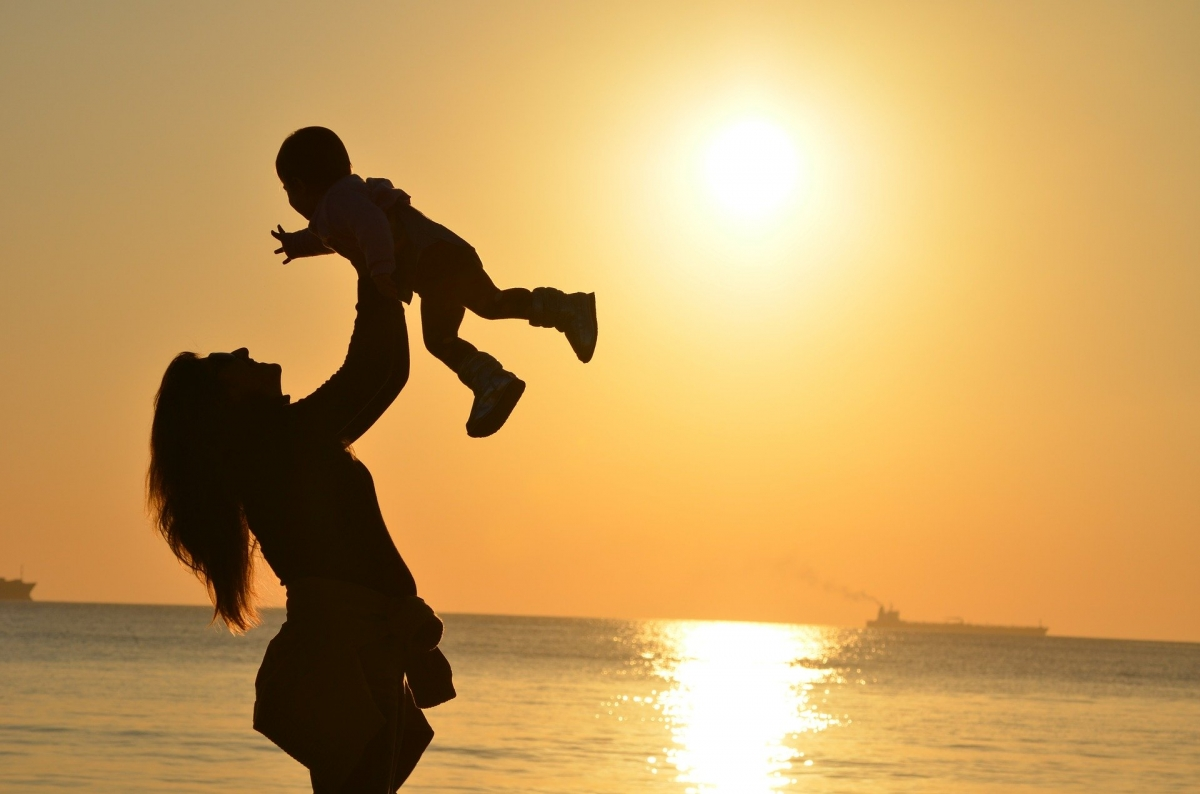 mother holds child at a beach sunset