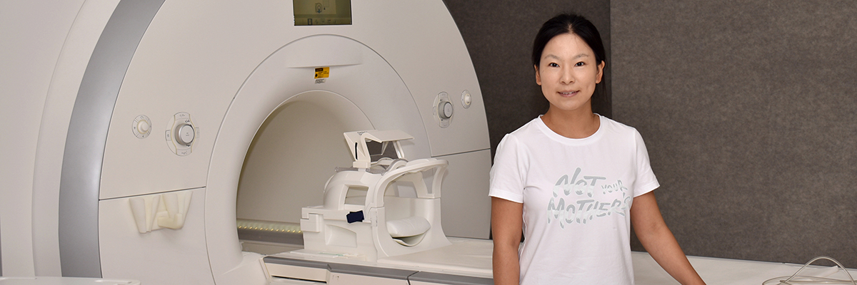 Xingjie Chen stands at MRI scanner