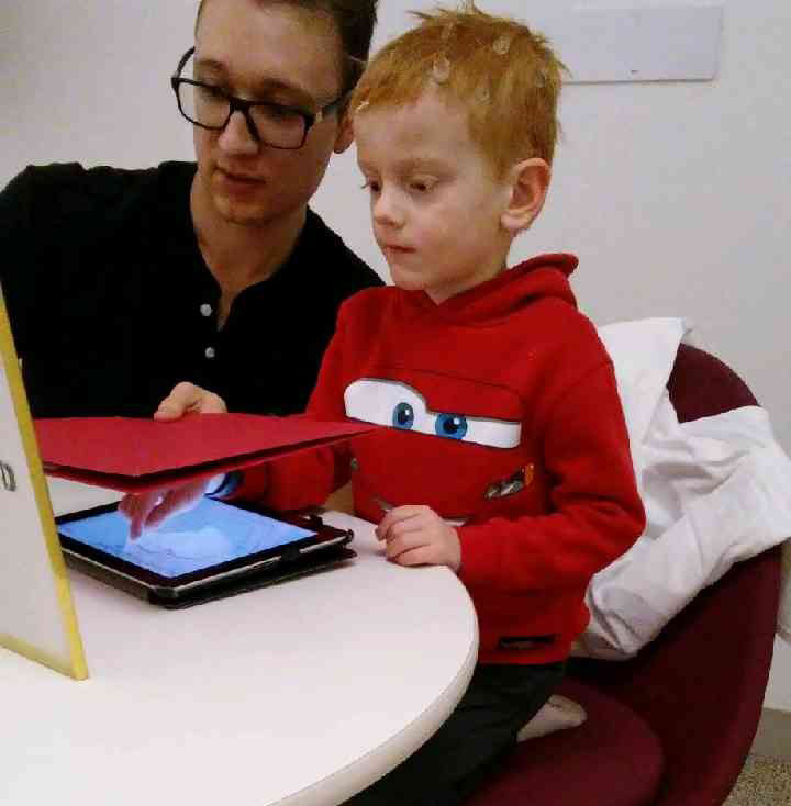 student works with child on IPad