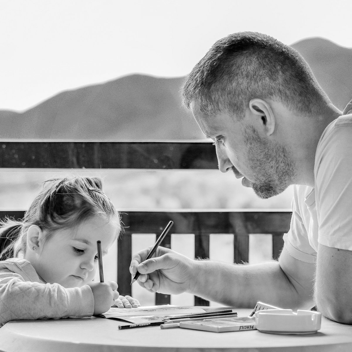 father and young daughter draw on paper