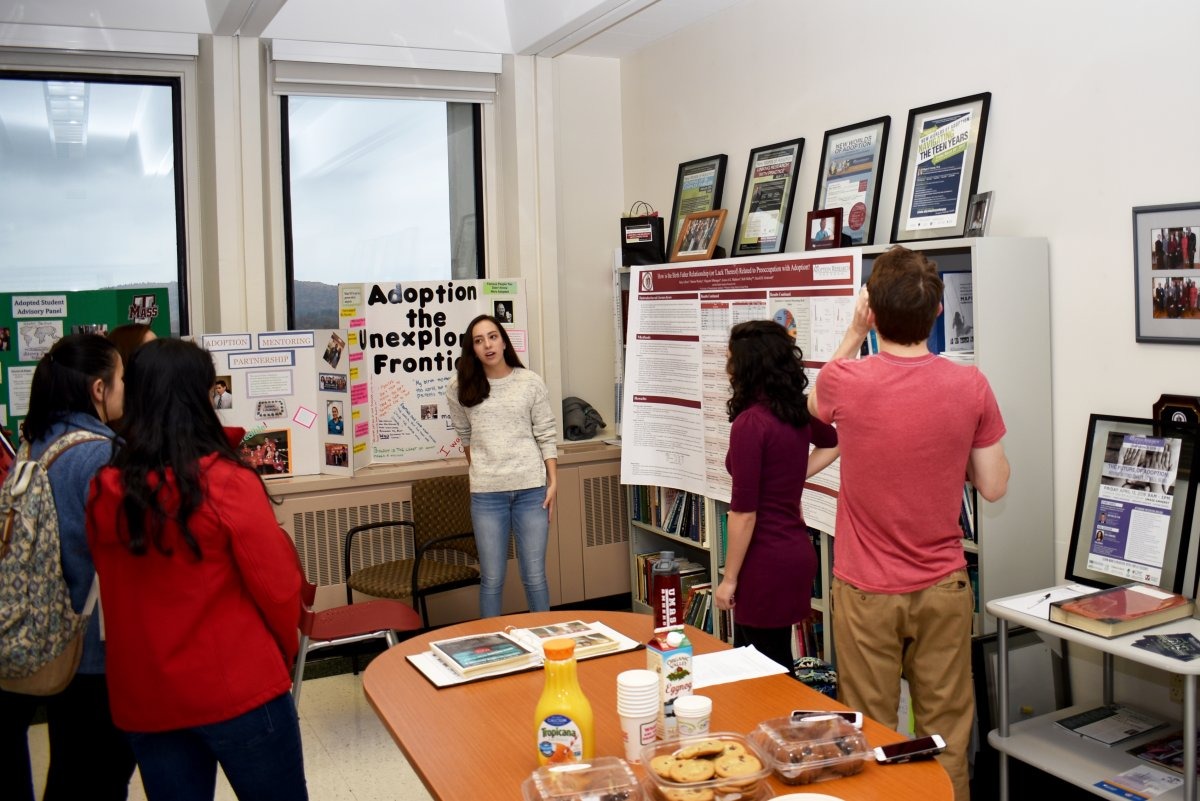 student presents adoption research with poster