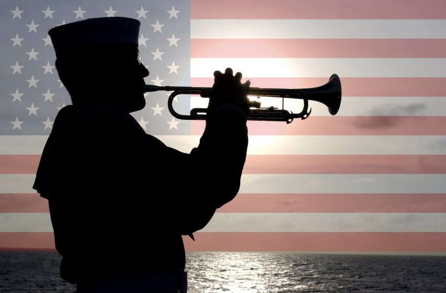 naval soldier plays trumpet in front of american flag