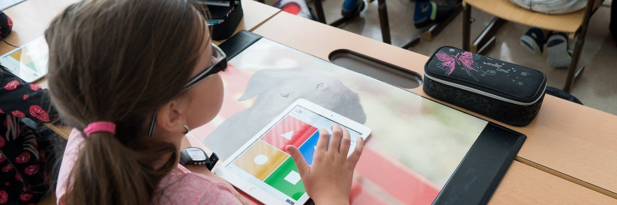child uses ipad in classroom